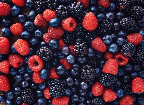 istock blueberies, raspberries and black berries shot top down 485349336
