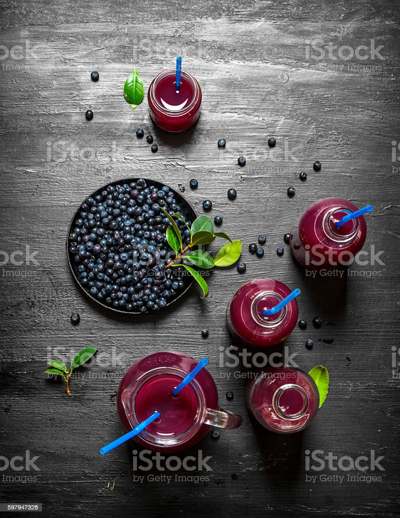 Blueberries and blueberry juice. On black wooden background. foto royalty-free