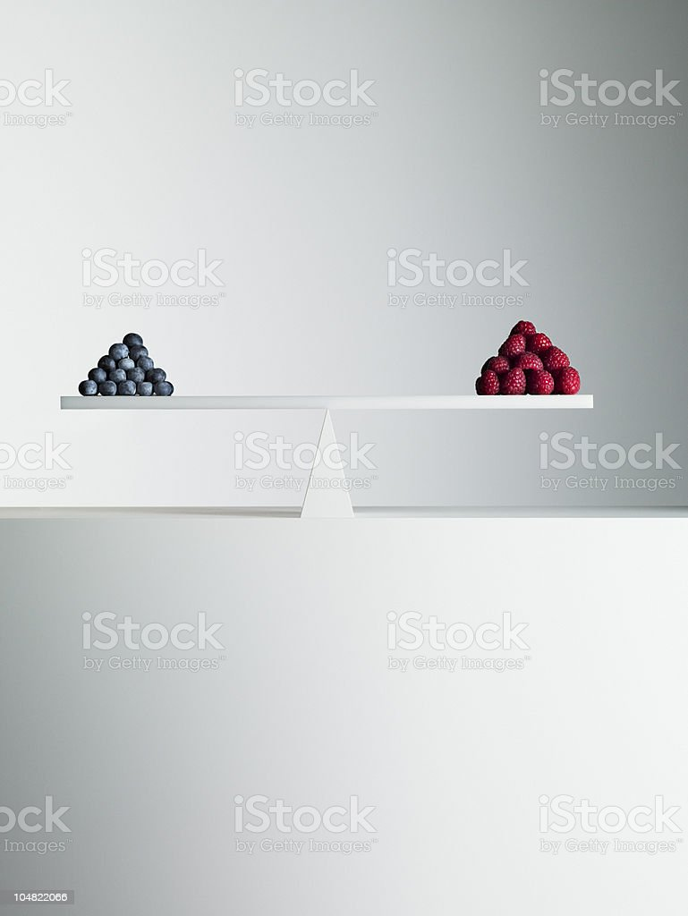 Blueberries and strawberries balanced on opposite ends of seesaw stock photo