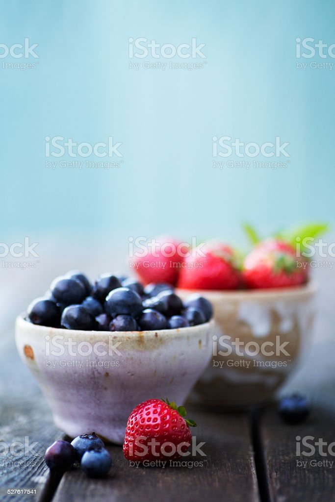 Blueberries and Strawberries in a Ceramic Bowl stock photo