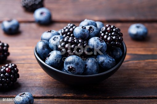 istock Blueberries, blackberries in black bowl on wooden background 915357780