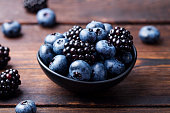 Blueberries, blackberries in black bowl on wooden background