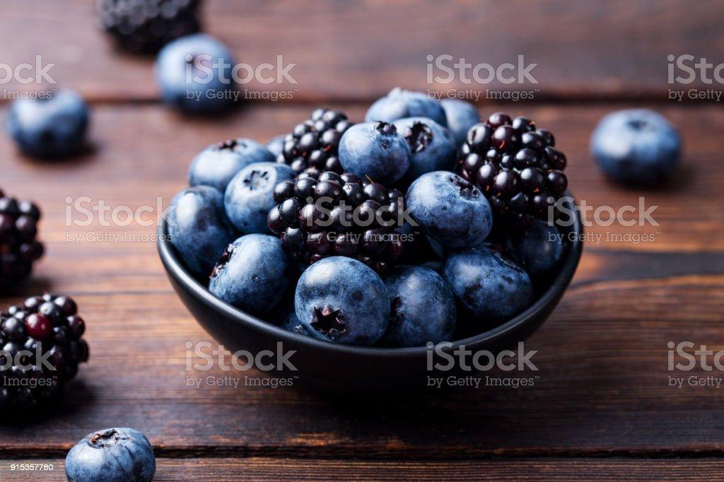Blueberries, blackberries in black bowl on wooden background stock photo