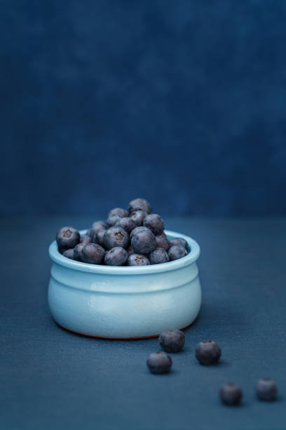 Blueberries in a blue bowl on a blue background stock photo