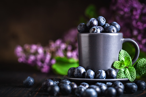 499658564 istock photo Blueberries in a Cup on a dark background. Summer and healthy food concept. Background with copy space. Selective focus. Horizontal. 1156084487