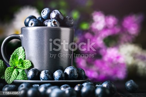 499658564istockphoto Blueberries in a Cup on a dark background. Summer and healthy food concept. Background with copy space. Selective focus. Horizontal. 1158445957