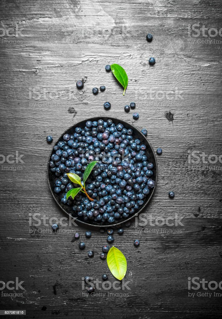 Blueberries in an old plate of leaves. stock photo