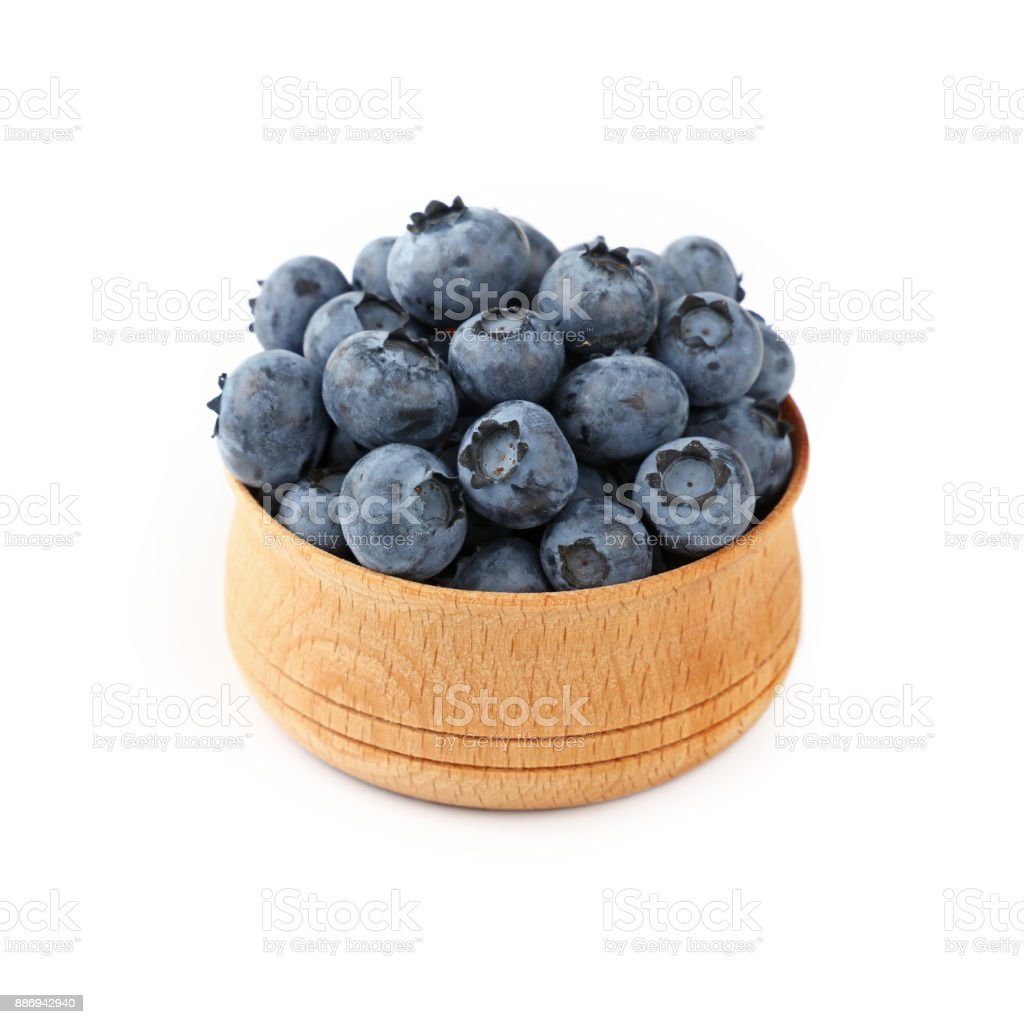Blueberries in wooden bowl close up over white stock photo