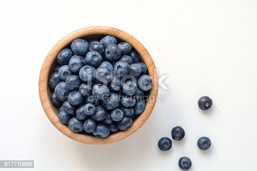 828761410 istock photo Blueberries in wooden bowl on white 817710696