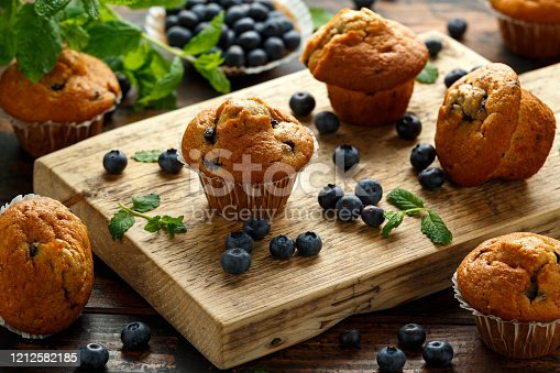 Blueberries muffins, cupcake with mint and berry on wooden board