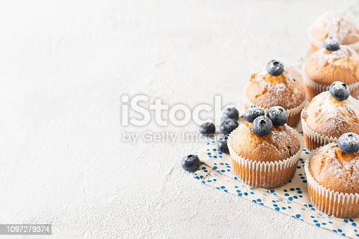 istock Blueberries muffins or cupcakes on white texture 1097279374