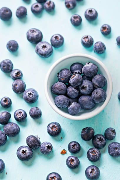 Blueberries on blue background page layout Blueberries on blue background page layout fruit carton stock pictures, royalty-free photos & images
