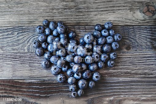 Blueberries on rustic wooden cozy background. Fresh-gathered berries full of vitamins, good for diet nutrition and healthy meals. Heart as a symbol of love and romance.