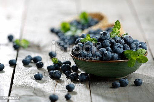 Full of blueberries close at the wooden table