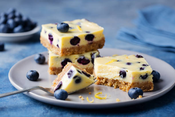 Blueberry bars, cake, cheesecake on a grey plate on blue stone background stock photo