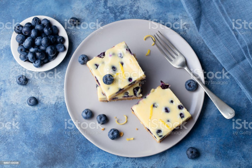 Blueberry bars, cake, cheesecake on a grey plate on blue stone background. Top view stock photo