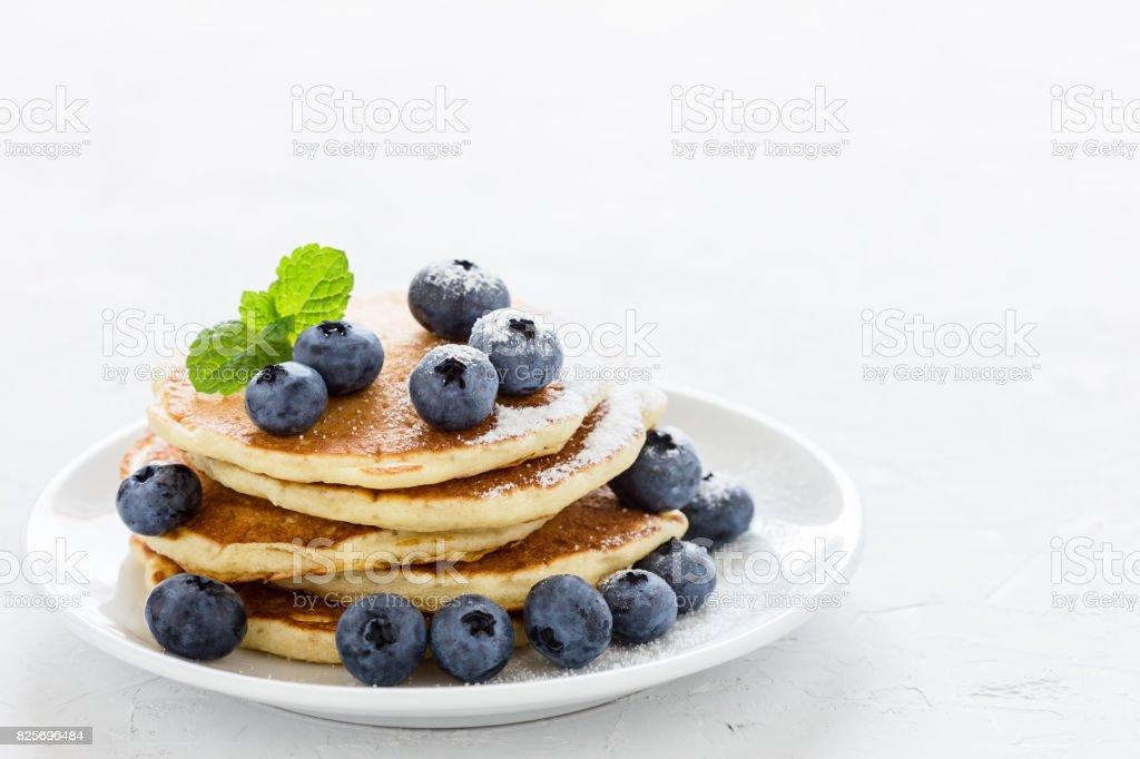 Blueberry buttermilk pancakes on white plate stock photo