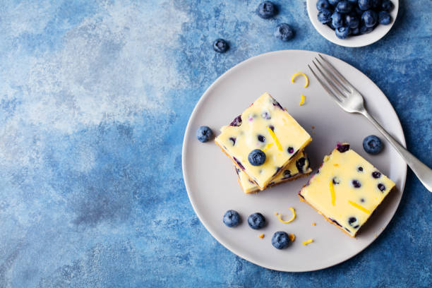 Blueberry cake, cheesecake on a plate. Blue stone background. Copy space. Top view. stock photo