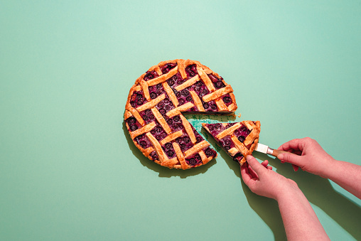 Above view with a woman's hands grabbing a slice of blueberries tart. Delicious homemade pie with a lattice crust and blueberries filling