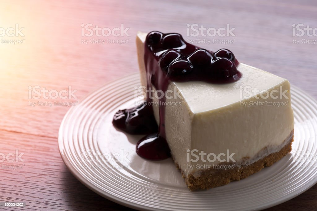 Blueberry cream cheesecake in white plate on wood table stock photo