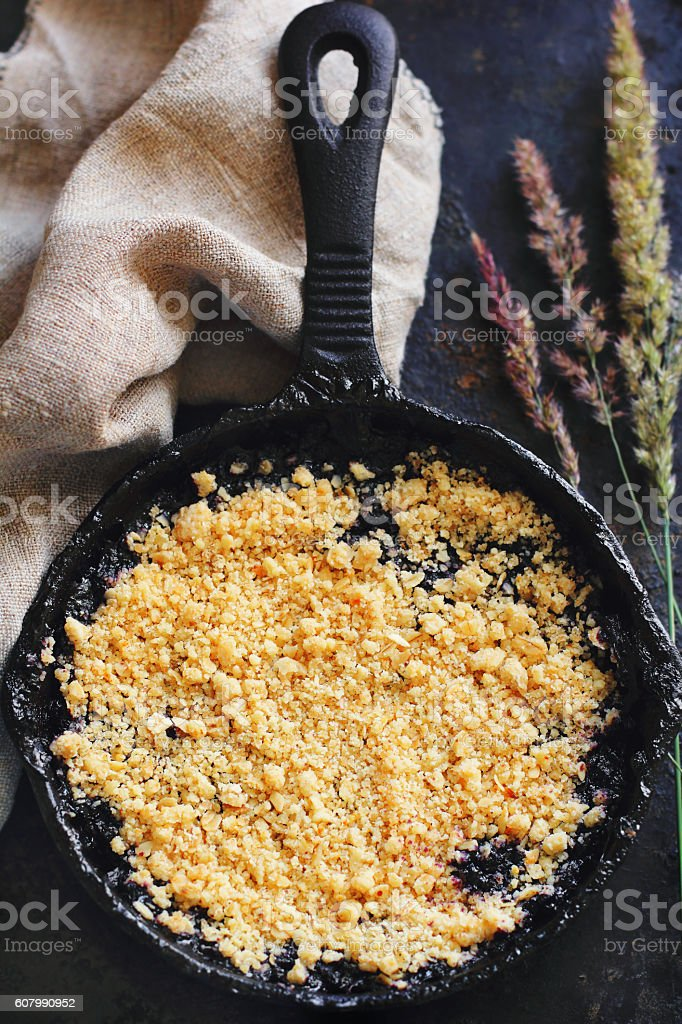 blueberry crumble in a cast iron pan stock photo