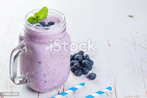 648804276 istock photo Blueberry jogurt smoothie in glass jar 648803560