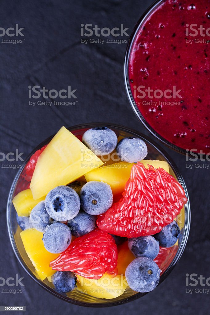 Blueberry, mango and grapefruit smoothie  on black background royaltyfri bildbanksbilder