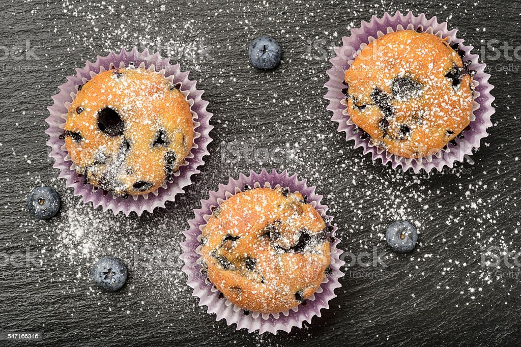 Blueberry muffins and blueberries on black background. stock photo
