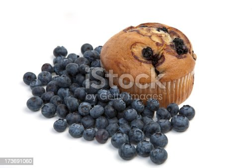 Blueberry muffin isolated on white with blueberries scattered around.