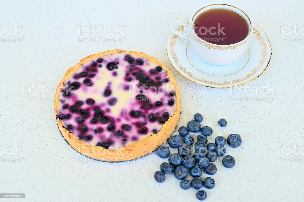 Blueberry pie, cup of tea and heap of blueberries on a white background - close up stock photo