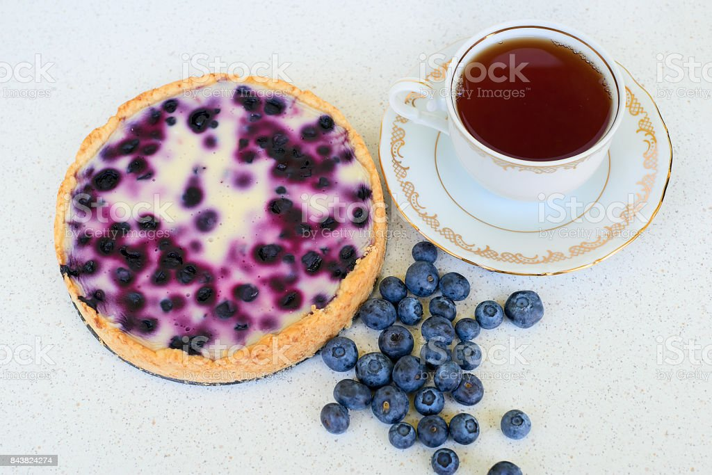 Blueberry pie, cup of tea and heap of blueberries on a white background - directly above stock photo