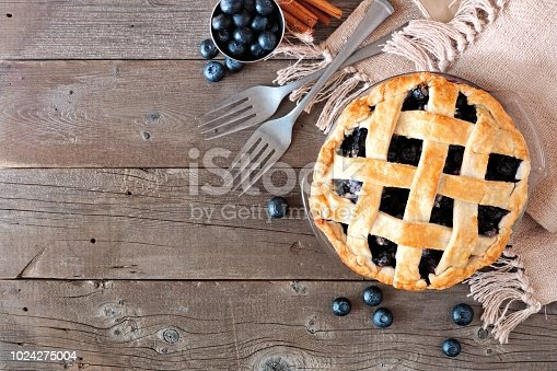 istock Blueberry pie, top view corner border over a rustic wood background 1024275004