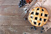 Blueberry pie, top view corner border over a rustic wood background