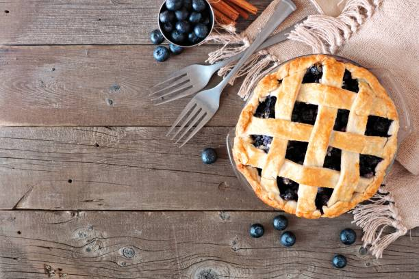 blueberry pie, top view corner border over a rustic wood background - blueberry pie stock pictures, royalty-free photos & images