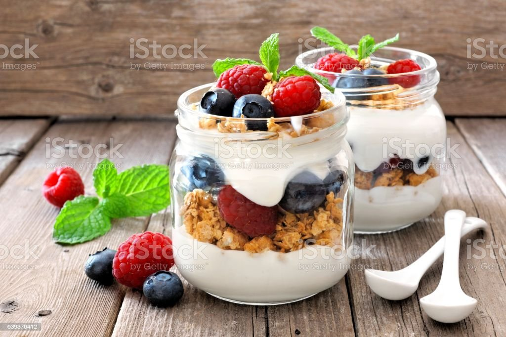 Blueberry, raspberry parfaits in mason jars, still life against wood stock photo