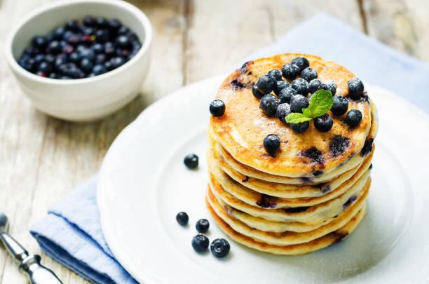 ブルーベリーリコッタチーズのパンケーキ、フレッシュブルーベリーとコーヒーカップ - パンケーキ ストックフォトと画像