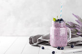 Blueberry smoothie in a glass jar garnished with berries, horizontal copy space