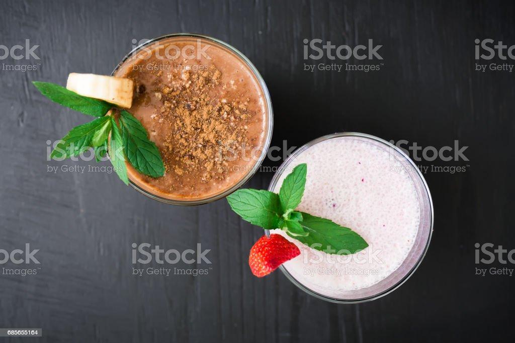 Blueberry smoothie with strawberry and banana smoothie on dark wood background. Fresh milkshake royalty-free 스톡 사진