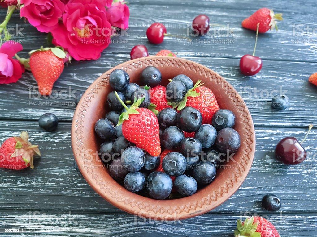 blueberry, strawberry cherry rose flower on old black wooden - Royalty-free Acima Foto de stock