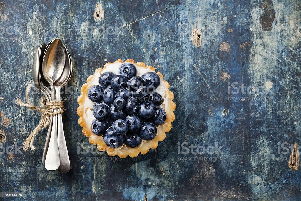Blueberry tart and teaspoons stock photo