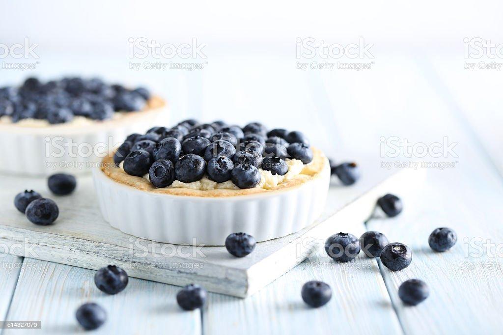 Blueberry tart on blue wooden table stock photo
