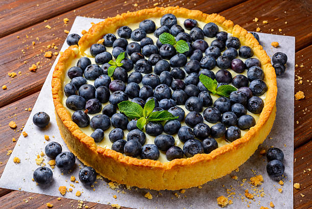 blueberry tart on vintage wooden background - blueberry pie stock photos and pictures