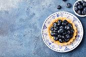 Blueberry tartlet, pie, tart with vanilla custard. Blue stone background. Top view Copy space.