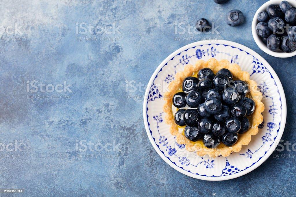Blueberry tartlet, pie, tart with vanilla custard. Blue stone background. stock photo
