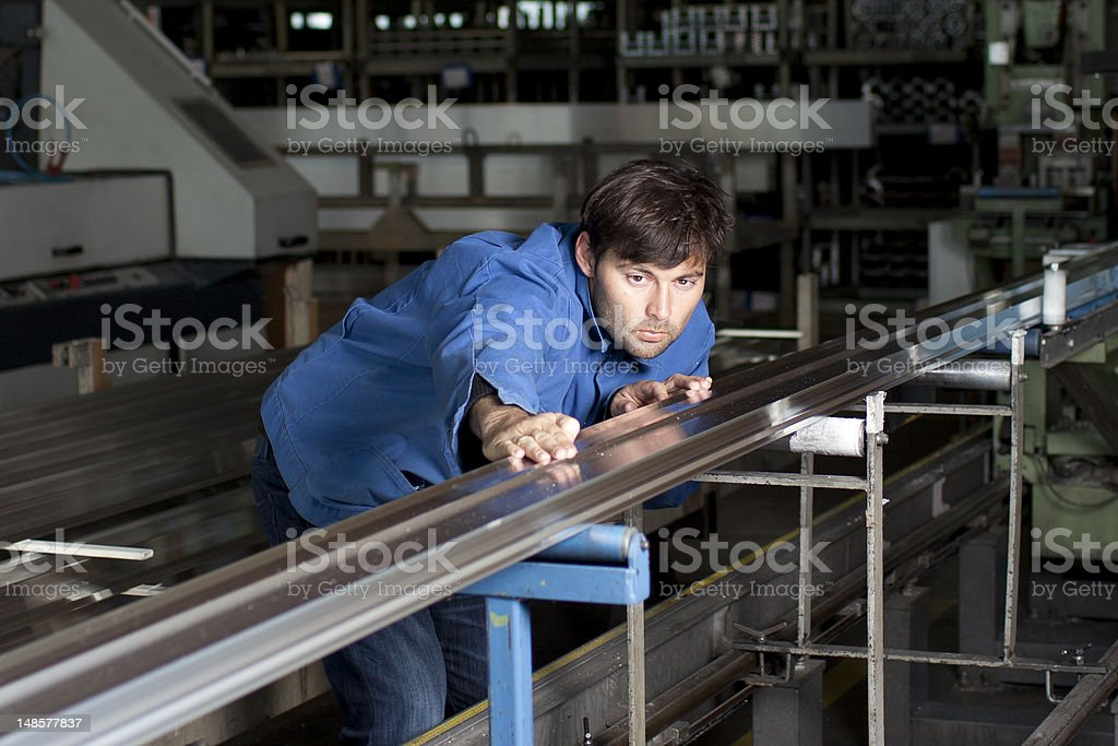 Blue-collar worker working in fabric stock photo