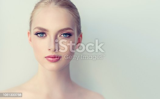 istock Blue-eyed, appealing woman in a expressive makeup and rose lipstick on lips is looking straight on viewer. Cosmetology. 1051333758