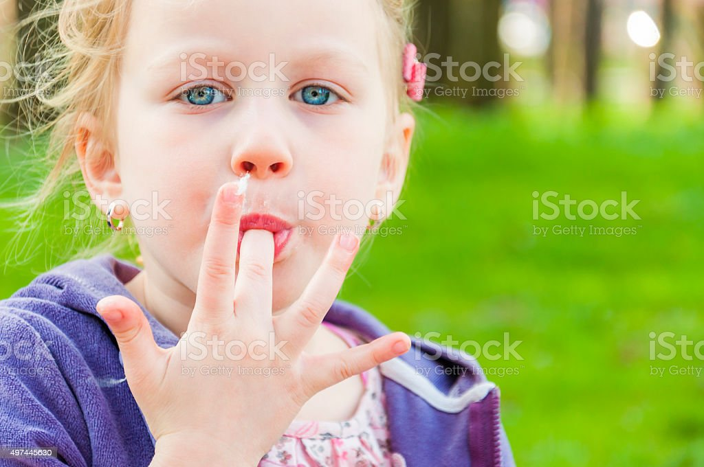 Blue-eyed blonde girl sucking long finger with candy-floss stock photo