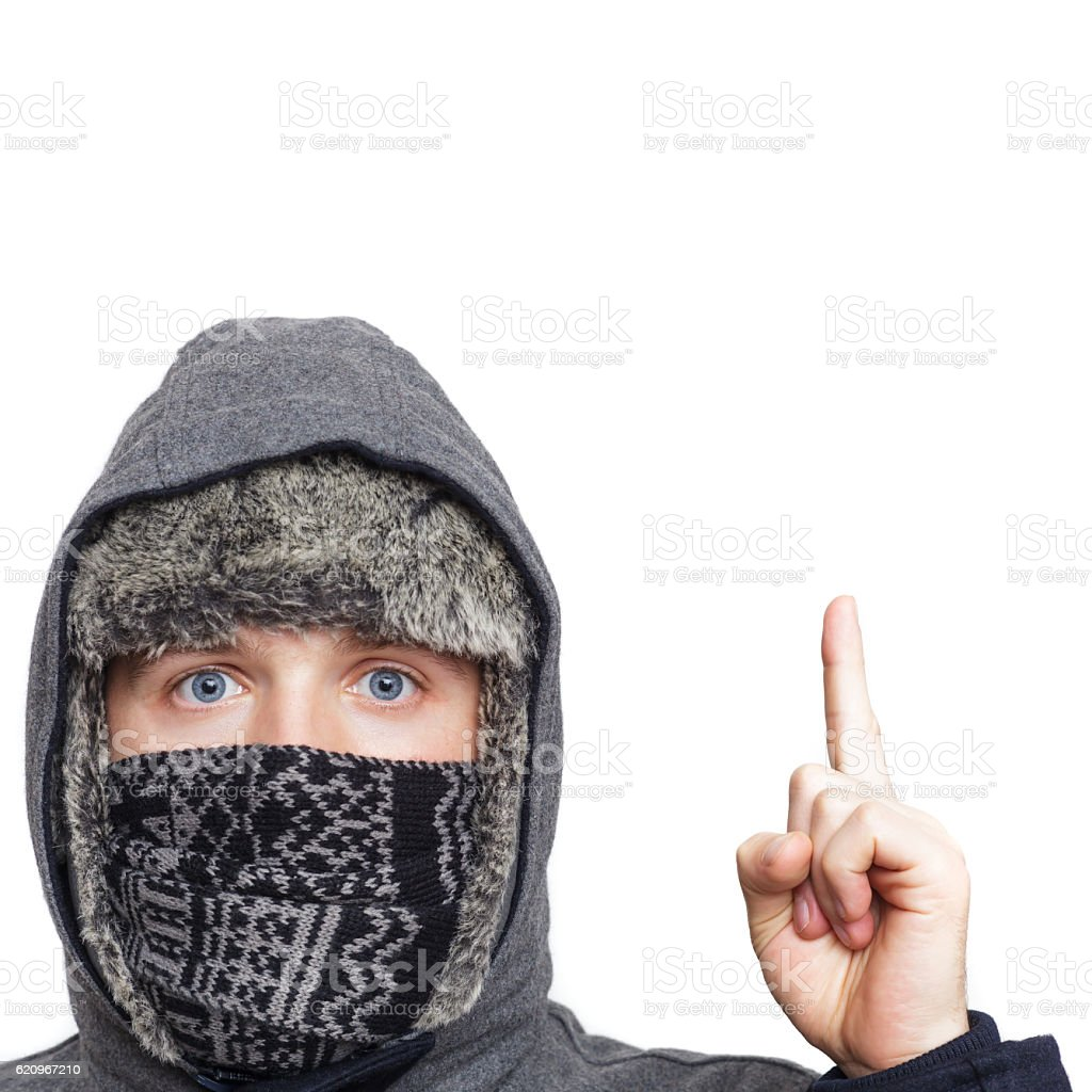 Blue-eyed boy wrapped in hood gives advice. Index finger upwar stock photo
