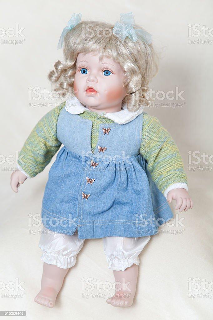Blue-eyed girl doll sitting on soft light background stock photo