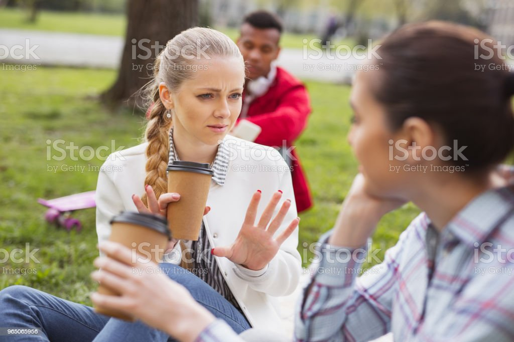 Blue-eyed student feeling emotional speaking with schoolmate royalty-free stock photo